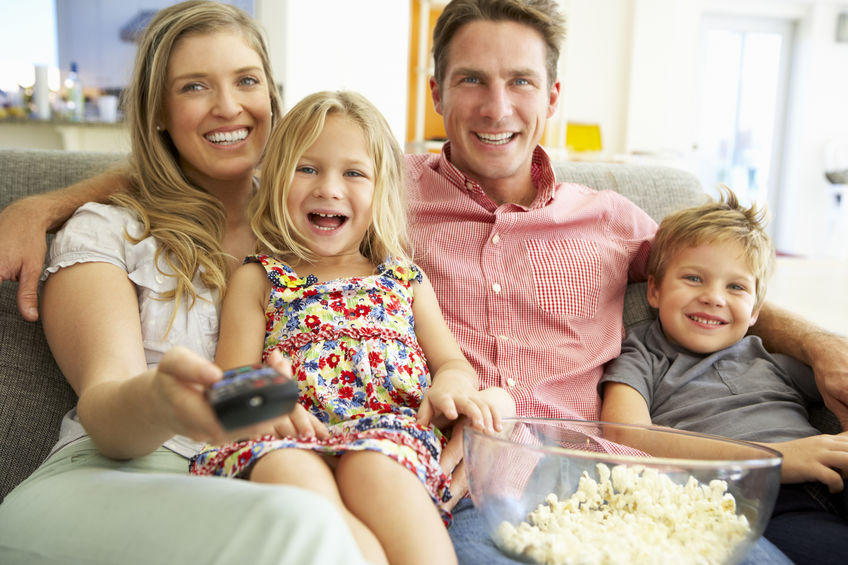 Family watching a film with popcorn