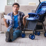 Young father assembling baby pram at home